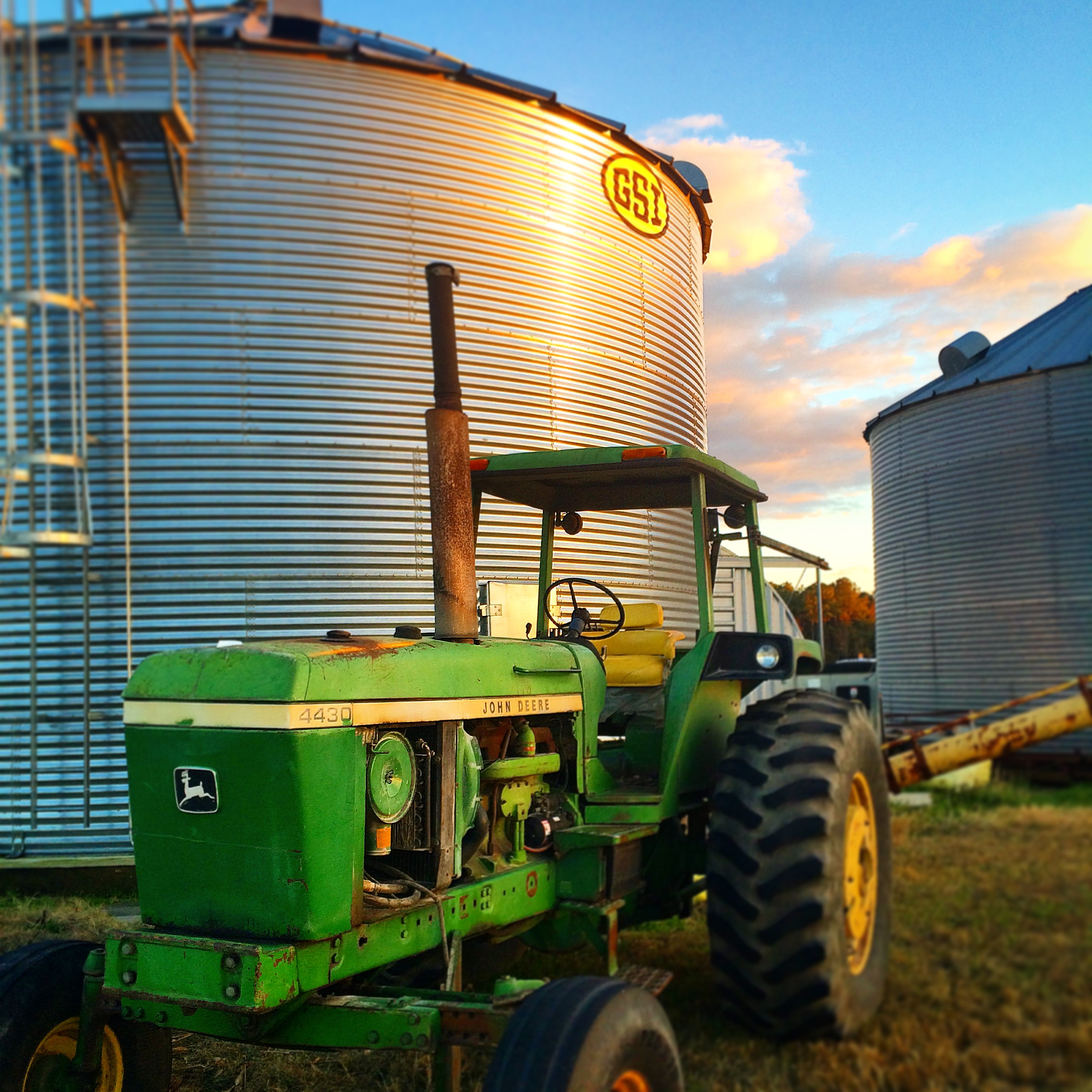 John Deere tractor in front of a corn silo
