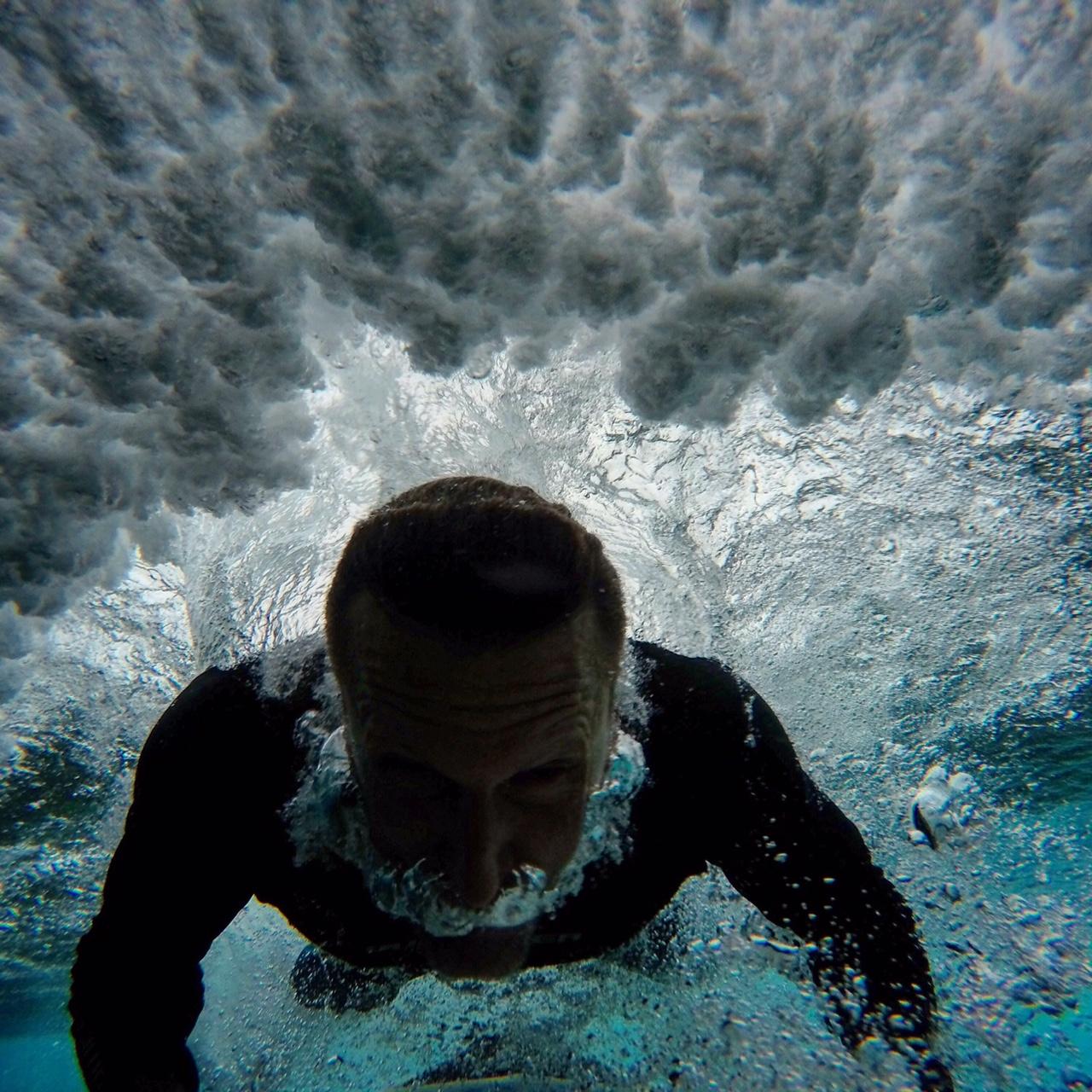 Surfer duck dives in Fiji