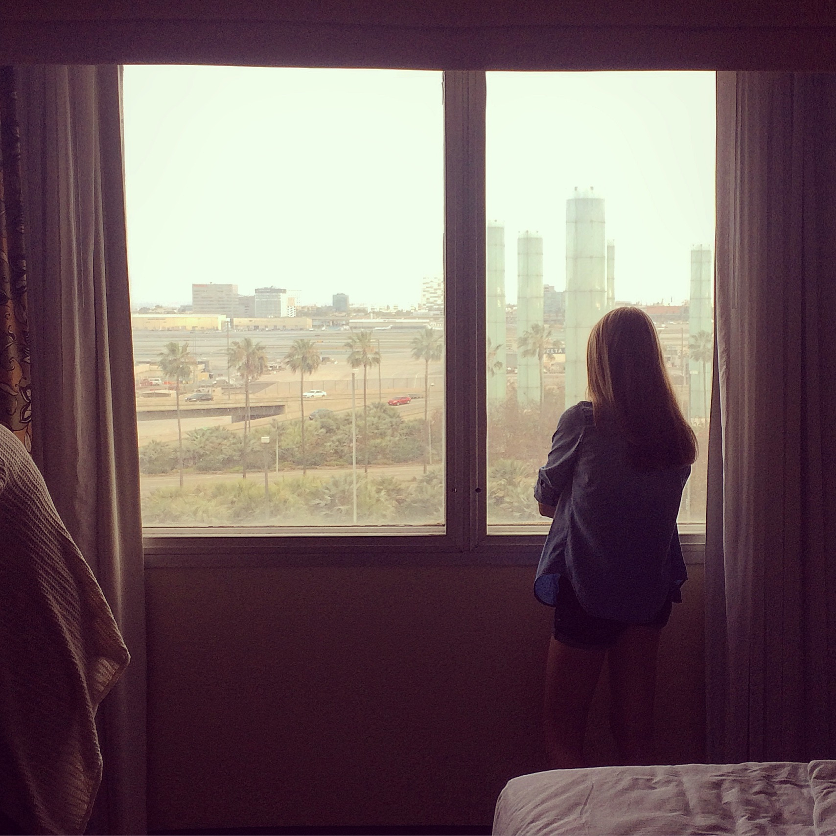 Kendall, gazing out the hotel window at the hazy LA skyline, prior to leaving for Fiji.