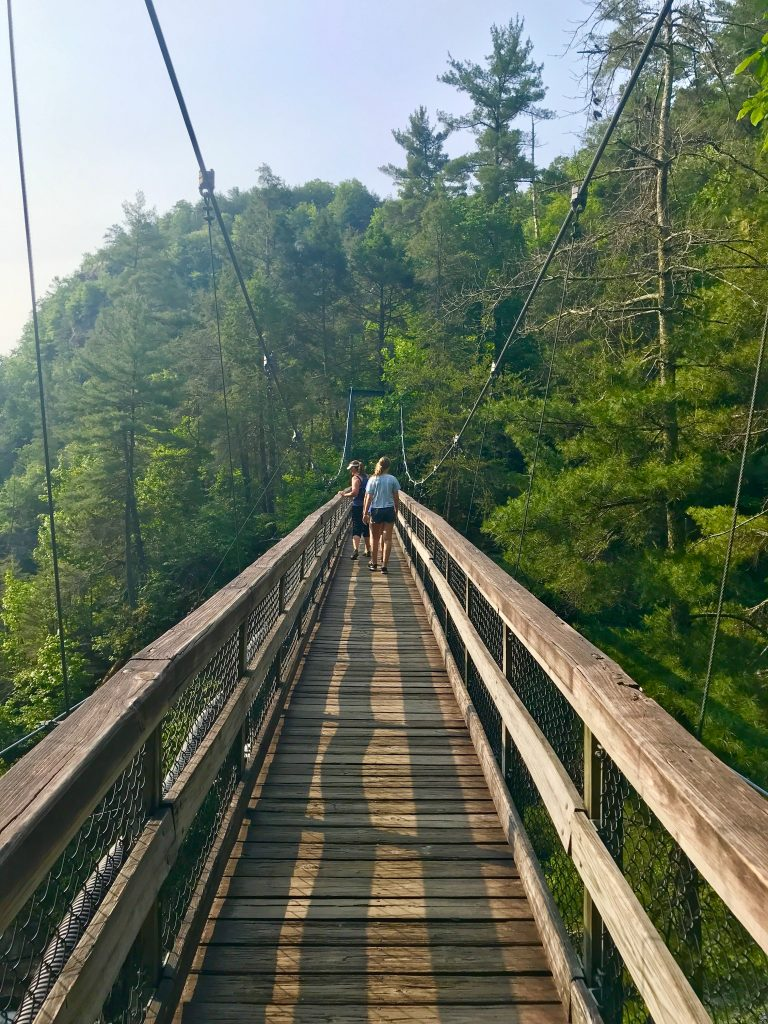 People walking across suspension bridge over Tallulah Gorge