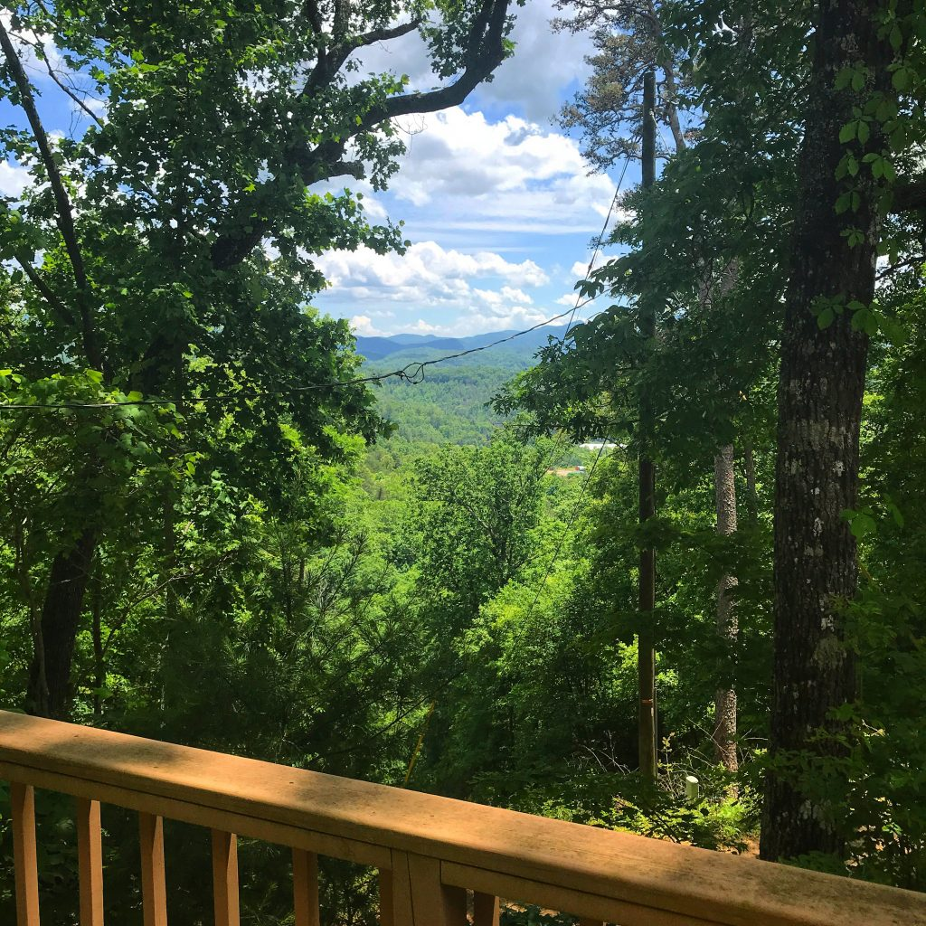 View through the forest to the mountains from the deck of a cabin in Franklin, NC