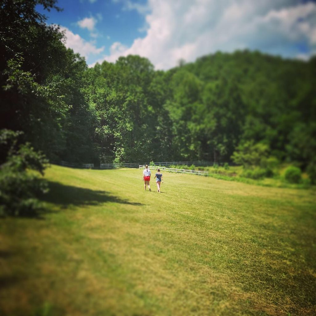 Girls walking across beautiful field with rolling hills at Highlands Aerial Park in North Carolina.