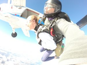 Girl laughing after just exiting the plane on a tandem skydive as plane turns away above the jumpers