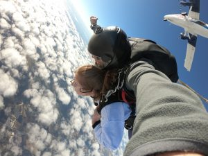 Skydiving girls falling, as plane above them turn away after exit
