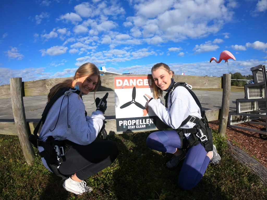 """Two girls pointing to a """"Danger"""" sign before skydiving at Zephryhills, FL"""