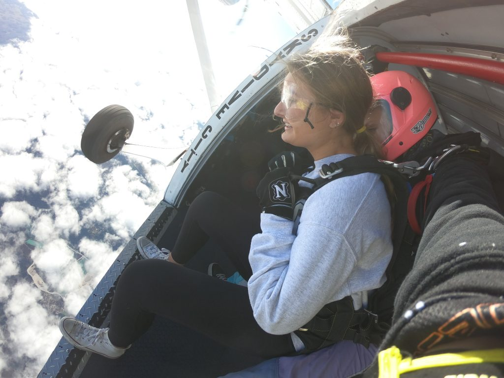 Girl about to exit airplane for a skydive, standing at the door looking down